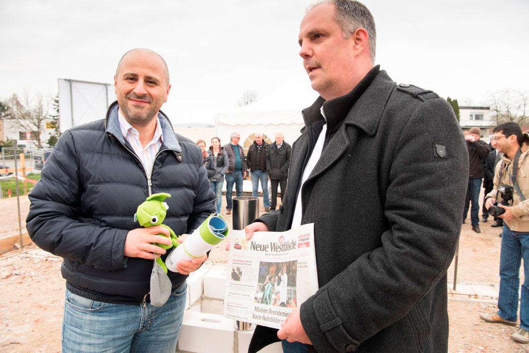 Stefan Bangel und Petros Jossifidis mit aktueller Ausgabe der NW, Unternehmensbroschüren und dem Unternehmensmaskottchen Egino