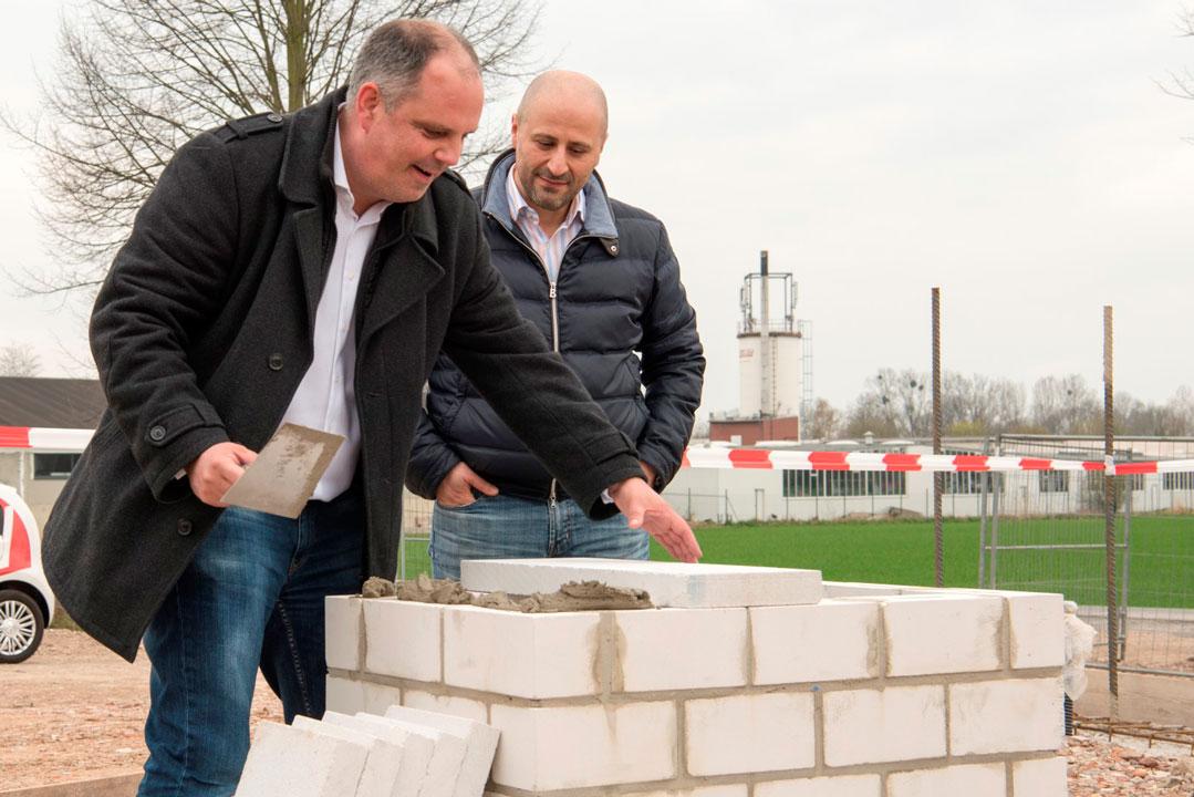 Stefan Bangel trägt mit sicherer Hand den ersten Mörtel auf den Grundstein auf.